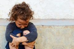 Niña pobre, triste contra el muro de cemento Fotografía de archivo