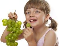 Niña que come las uvas de un vino Fotografía de archivo