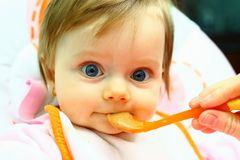 Niña que come los alimentos para niños Imagen de archivo
