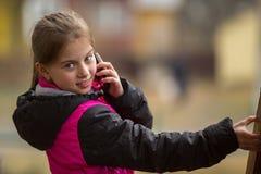 Niña que habla en el teléfono móvil Foto de archivo