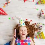 Niña que habla por el teléfono móvil a sus amigos en cumpleaños Imagen de archivo