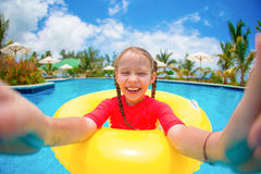 Niña que hace el selfie en el anillo de goma inflable que se divierte en piscina Fotografía de archivo libre de regalías