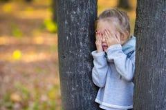 Niña que juega escondite cerca del árbol Foto de archivo