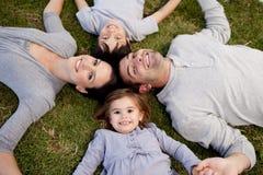 Niña que miente en un parque con su familia Imagen de archivo libre de regalías