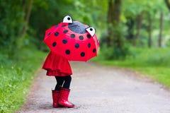 Niña que recorre en la lluvia Fotos de archivo