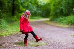 Niña que recorre en la lluvia Imagenes de archivo