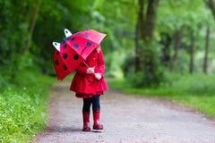 Niña que recorre en la lluvia Fotografía de archivo libre de regalías