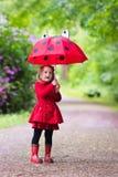 Niña que recorre en la lluvia Fotos de archivo libres de regalías