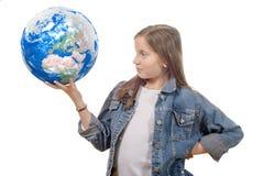 Niña que sostiene un globo del mundo, aislado en un backgroun blanco Fotos de archivo libres de regalías