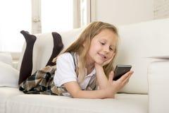 Niña rubia feliz en el sofá casero usando Internet app en el teléfono móvil Fotos de archivo libres de regalías