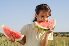 Niña sonriente con dos rebanadas de sandía Imagen de archivo