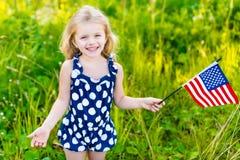 Niña sonriente con el pelo rubio largo que sostiene la bandera americana Foto de archivo libre de regalías