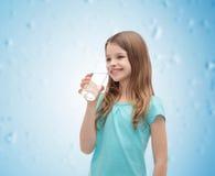 Niña sonriente con el vidrio de agua Imagen de archivo libre de regalías
