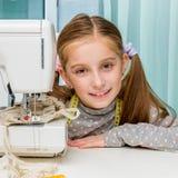 Niña sonriente en la tabla con la costura Foto de archivo libre de regalías