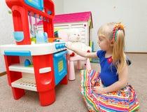 Niña trabajadora que cocina la comida en la estufa del juguete para su peluche Imagen de archivo libre de regalías