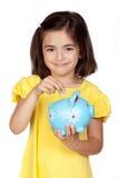Niña triguena con un moneybox azul Imagenes de archivo