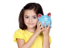 Niña triguena con un moneybox azul Fotos de archivo