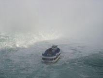 Niagara Falls. A picture of the Maid of the Mist boat which makes daily tours of Niagara Falls. The white at the top of the image is the spray from the water stock photography