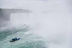 Niagara falls and boat on river. Niagara falls and boat full of people on river in mist major canadian american landmark Royalty Free Stock Image