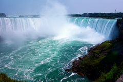 Niagara Falls. Canadian part of Niagara Falls has a horseshoe shape. powerful jets of turquoise water falling from a great height forming a high column of water Royalty Free Stock Image