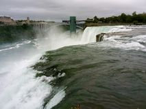 Water gushes over Niagara Falls - NY - USA. Niagara Falls is the collective name for three waterfalls that straddle the international border between the Canadian royalty free stock images