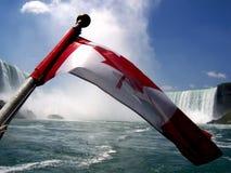 Niagara Falls con la bandera canadiense Imágenes de archivo libres de regalías