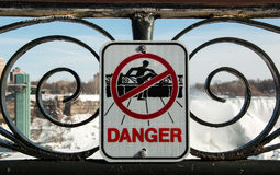 NIagara Falls Danger Sign. A sign warning of the danger of climbing over the safety rails along the Canadian side of Niagara Falls. Shot during winter royalty free stock photography