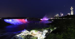 Niagara Falls illuminated at night. Horseshoe and American Falls, river and Niagara skyline illuminated at dusk, panoramic view, Canada royalty free stock photo