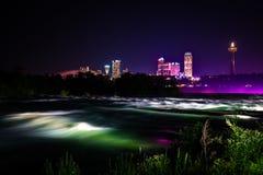 Niagara Falls iluminó con las luces del color en la noche foto de archivo