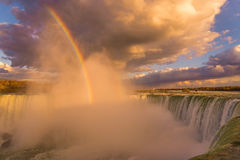 Niagara Falls lights up beautifully as the sun sets. Niagara Falls, Canadian side, glowing as the sun sets and a rainbow appears Stock Photography