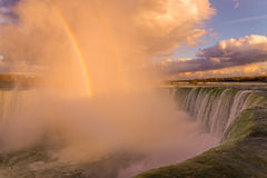 Niagara Falls lights up beautifully as the sun sets. Niagara Falls, Canadian side, glowing as the sun sets and a rainbow appears Stock Images