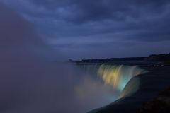 Niagara Falls lit at night by colorful lights Royalty Free Stock Photography