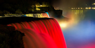 Niagara Falls lit at night show by colorful lights. Stock Photos