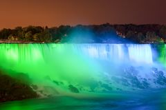 The Niagara Falls at night was illuminated by the lights. Niagara Falls is situated at the junction of Ontario, Canada and New York State of the United States royalty free stock photography