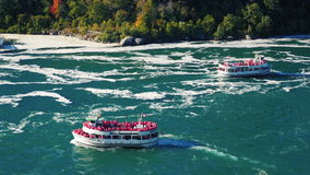 NIAGARA FALLS, NY - OKTOBER 20, 2016: Two ships are sailing with tourists on the Niagara River below Niagara Falls. View. Two ships are sailing with tourists on stock video footage