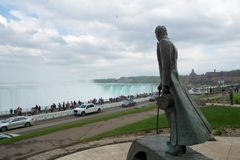 NIAGARA FALLS, ONTARIO, CANADA - MAY 21st 2018: Nikola Tesla sculpture in Queen Victoria Park with the Horseshoe falls. In the background. The monument was stock photography