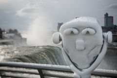 Niagara Falls Sightseeing Frozen Binoculars. Sightseeing tourist binoculars frozen in ice, overlooking Niagara Falls on a cold winter afternoon Royalty Free Stock Photo