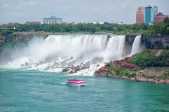 Niagara Falls. US part of the Niagara Falls, a cloud of spray from the falling water, rocky cliffs of the Niagara River covered with green plants. Tourist boat Stock Photography