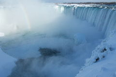 Niagara Falls in the winter. Niagara Falls, 27 February 2015, on a sunny day, partially frozen - with rainbow, and frozen waves Royalty Free Stock Photos