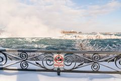 Niagara Falls in Winter with snow and ice. Danger sign on frozen railing at Niagara Falls, Canada royalty free stock photography