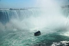 Niagara Horseshoe Falls with a touristic vessel Maid of the Mist approaching. The falls height is 57 m and they throw. Down about 6,400 m3 water per second stock photo