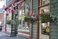 Niagara no lago, o 25 de junho: Armazene a entrada e a baixa canadense das bandeiras dentro do Niagara-em--lago da província de O Imagens de Stock