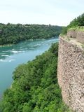 Niagara River Rapids NY. Just beyond the falls, a rock wall over looks the water and beginning of the whirlpool rapids Royalty Free Stock Image