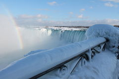 Niagara in the winter. Niagara Falls in the winter,  27 February 2015, on a sunny day, with a rainbow, and the rails completely frozen Stock Photo