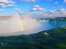 Niagaradalingen met een regenboog op een dag met blauwe hemel Canada stock fotografie