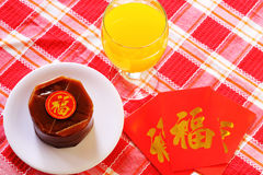 Nian Gao Chinese New Year special dishes. Nian Gao served at the table with a glass of orange juice and red packets. image is suitable for food and beverage