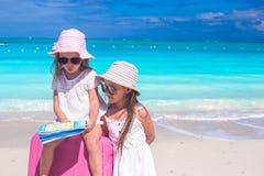 Niñas con la maleta y el mapa grandes en tropical Imagen de archivo libre de regalías