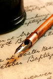 Nib Pen and Inkwell. Vintage nib pen and inkwell, on a page of 18th century script royalty free stock photos