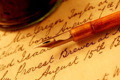 Nib Pen and Inkwell. Vintage wooden-handled nib pen and inkwell, on a page of 18th century script Stock Photos