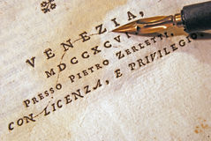 Nib (pen) over an old book. Wooden nib over an very old book Stock Images